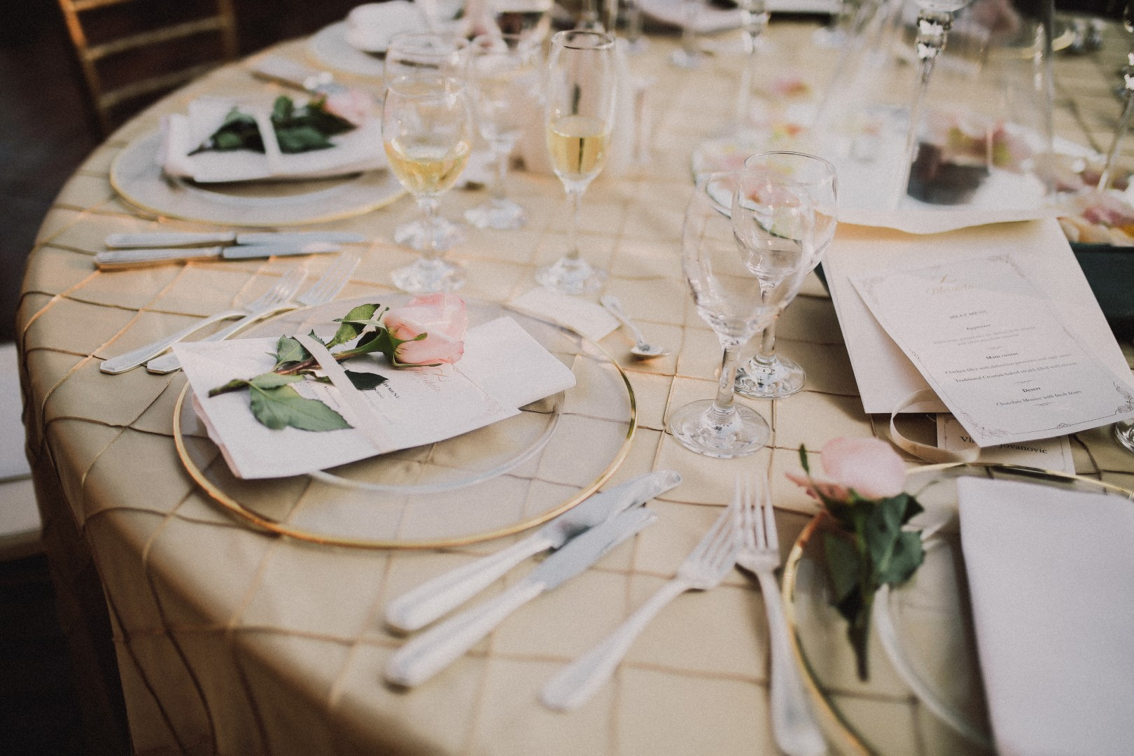 This is a close up of the wedding reception table. The tablecloth is blush as well as the flowers. Some of the flowers are white. There are plates and glasses as well as cutlery and menus.