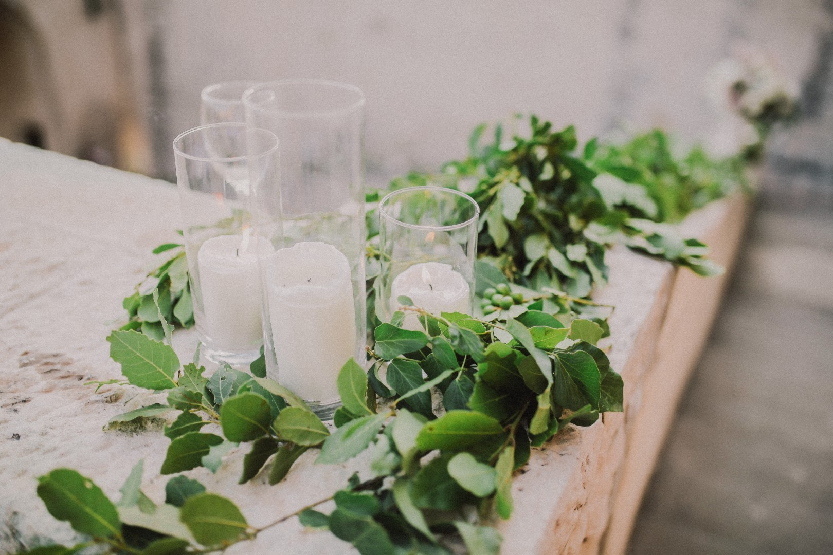 On this photo we can see some greenery and white candles as wedding decoration.