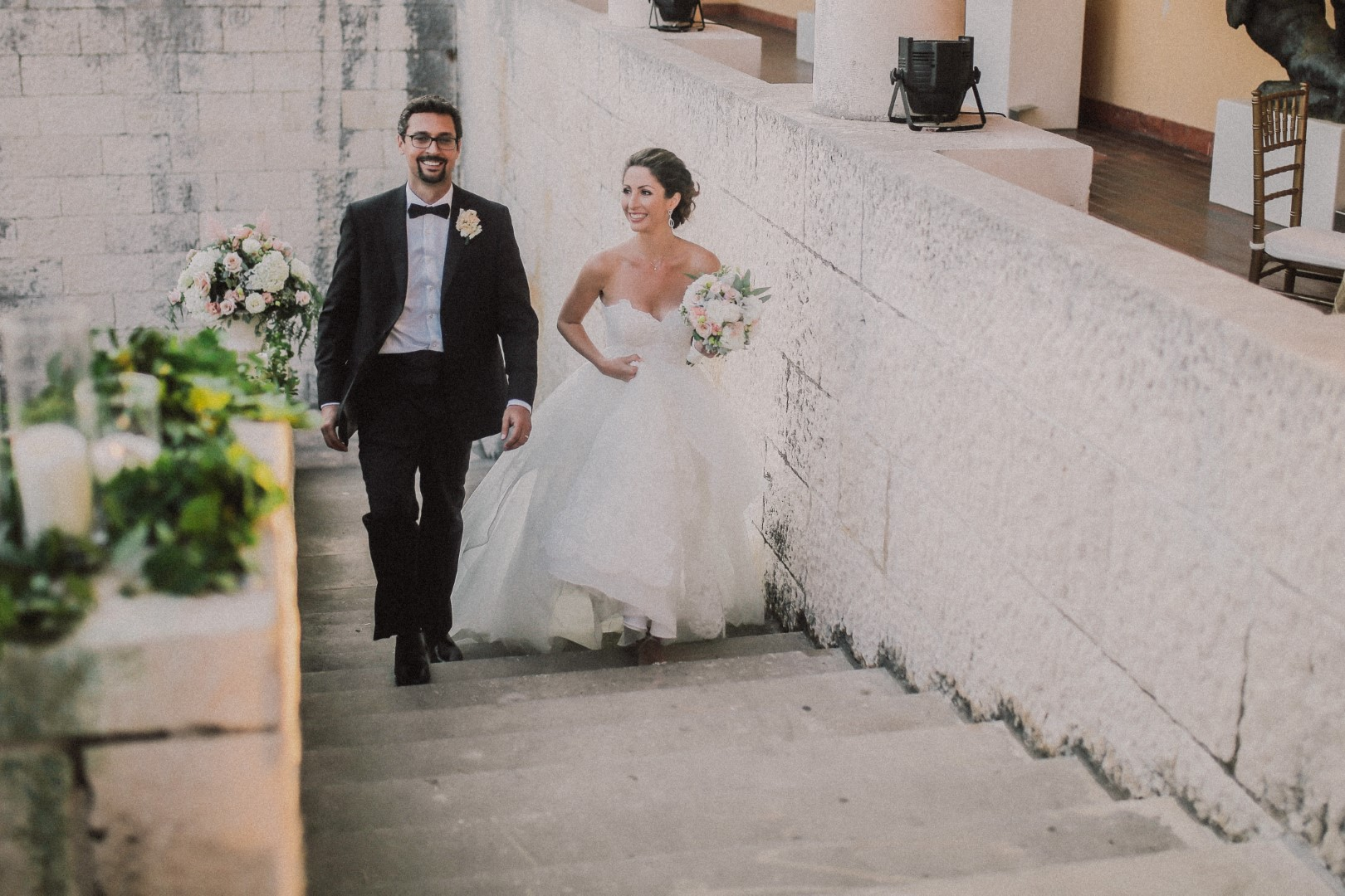 The couple is arriving to their wedding reception at the Dubrovnik art gallery. She is holding up her wedding dress and the bouquet in the other hand. The groom is laughing. On the stone wall next to the stairs is some greenery with simple white candles.