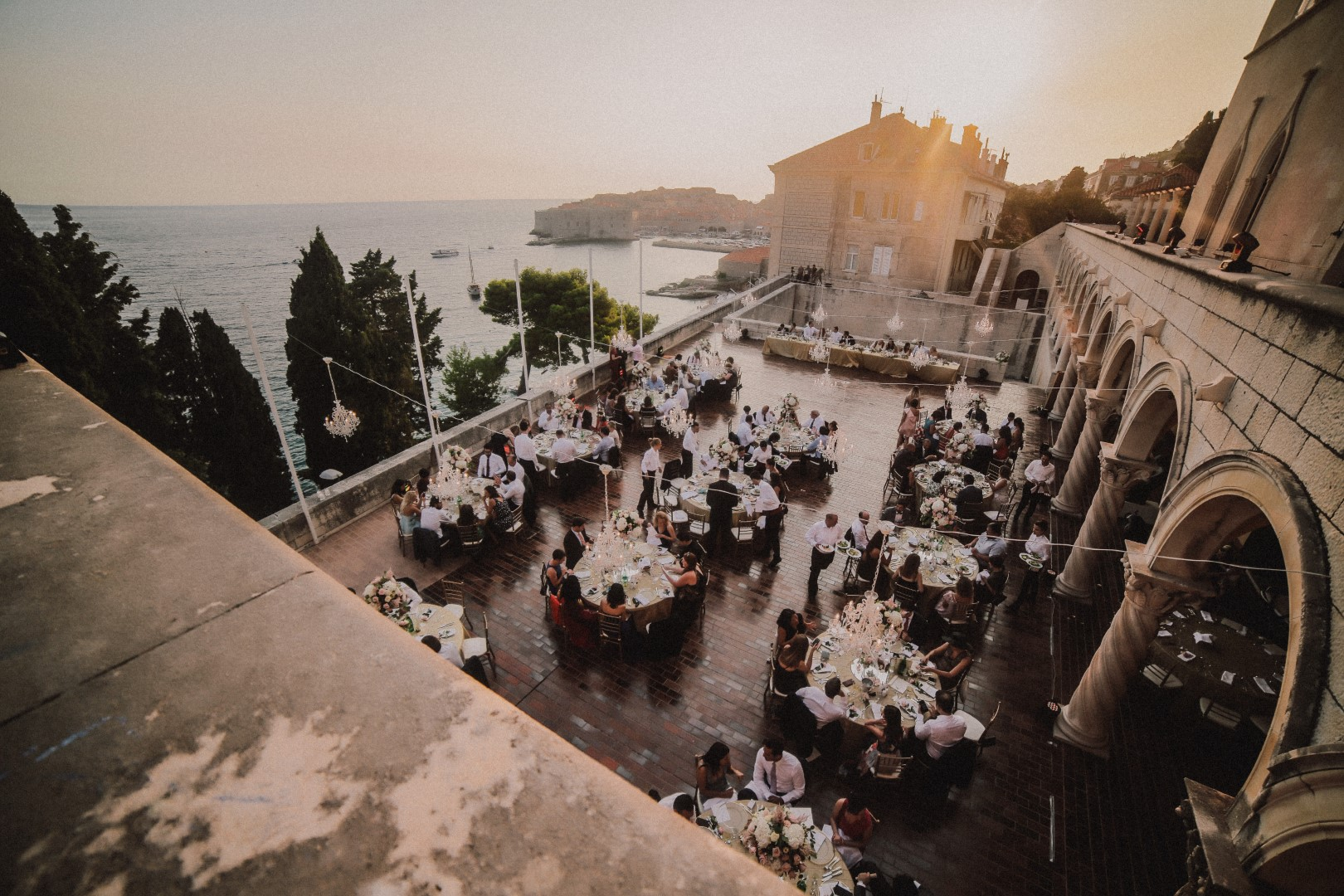 An aerial shot of the wedding reception on the terrace of the Dubrovnik art gallery. Dubrovnik old city is in the background. The tables are round and there are chandeliers hanging over them on a string. The guests are being served dinner while chatting.