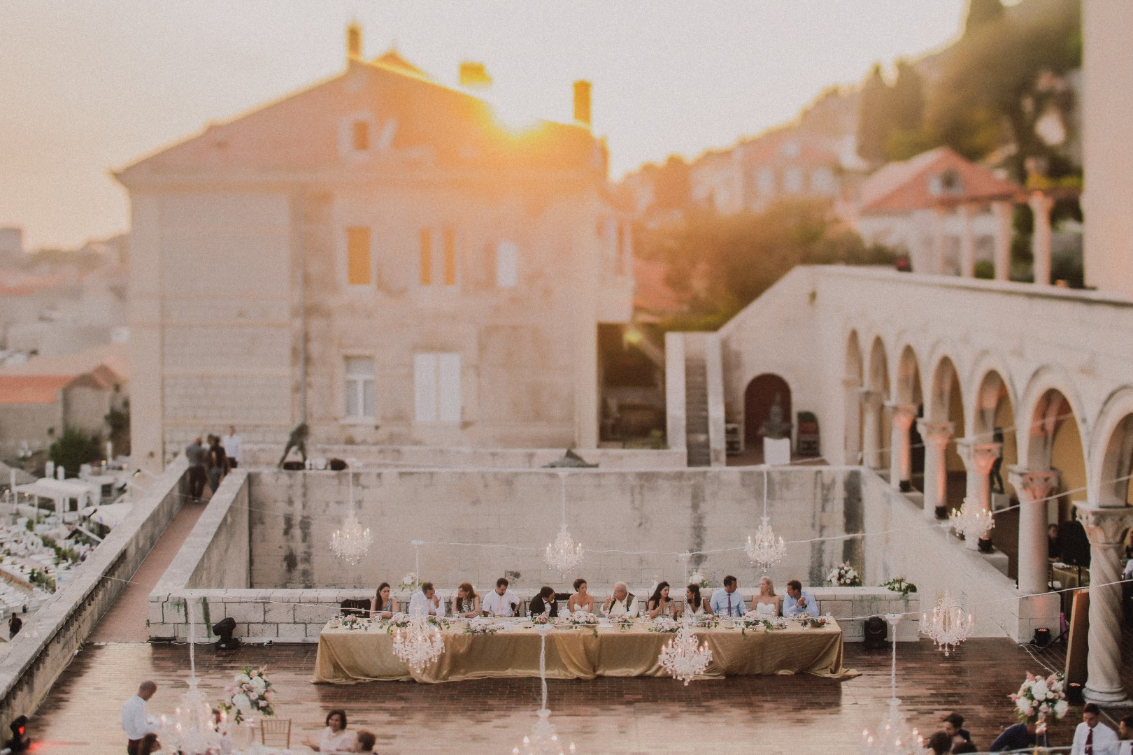 Aerial shot of the Dubrovnik art gallery terrace. On the right side are columns and on the left a view of the beach. In the middle is the top table with the bride, groom and their closest friends and family. Above them are chandeliers. The sun is setting.
