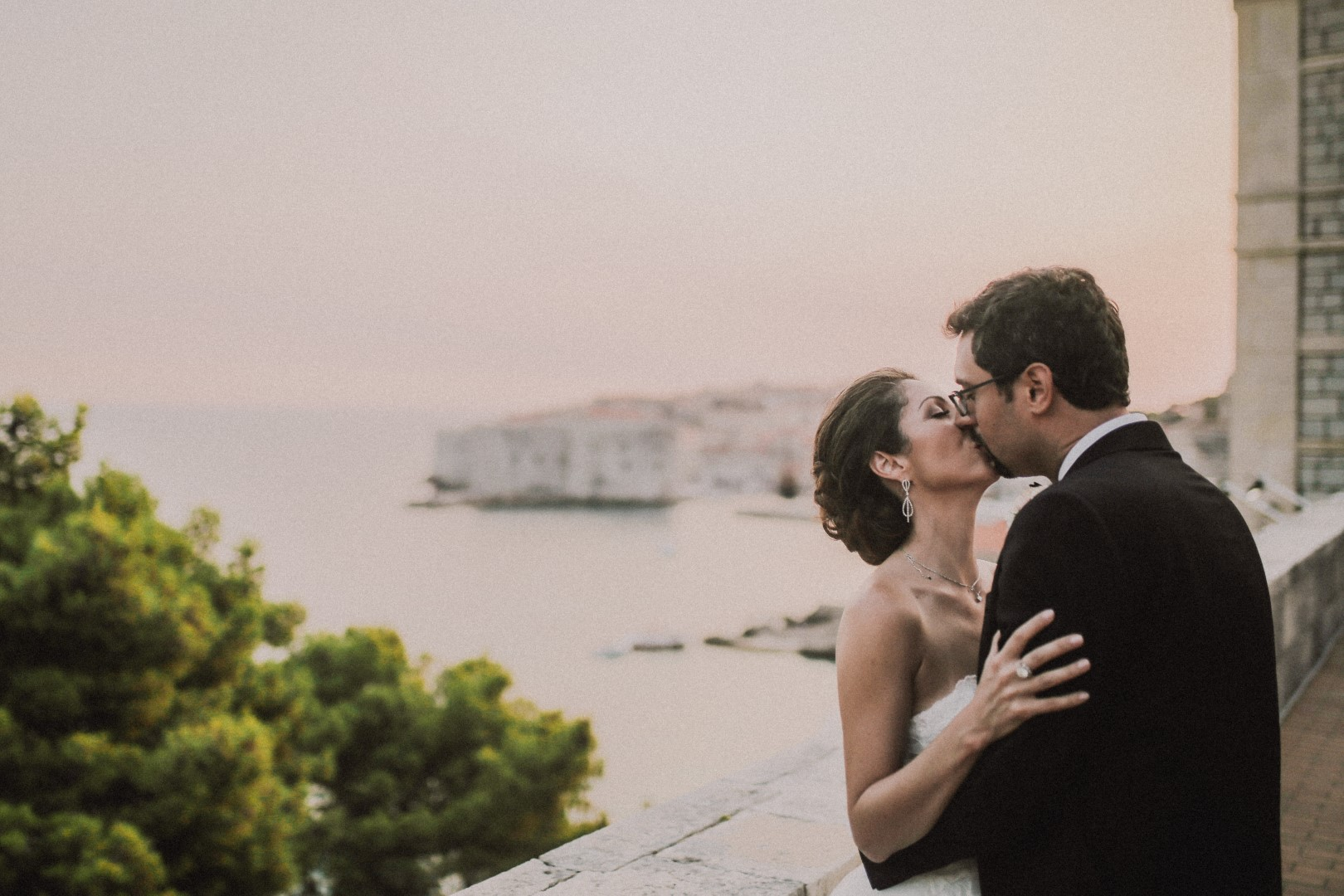 This is a photo of the happy couple kissing. In the background is the stunning view of Dubrovnik old town and the sea. She has an updo and he's wearing a classic black tux.