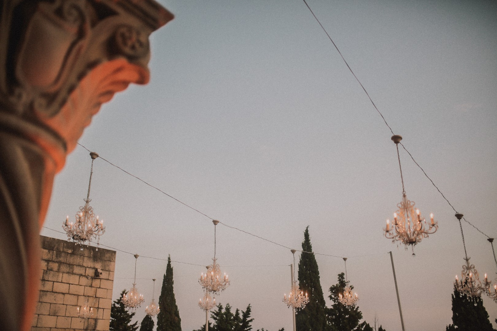 This photo is showing chandeliers hanging on a string tied between the columns. There is a little part of the column as well as tops of trees and the sky.