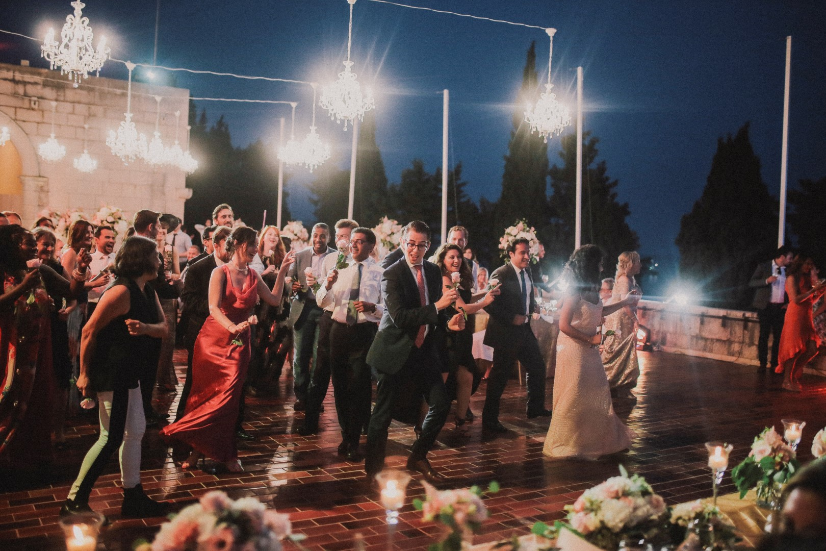 This photo is showing the wedding guests dancing at the art gallery in Dubrovnik. It looks like it's a choreography and everyone is laughing.