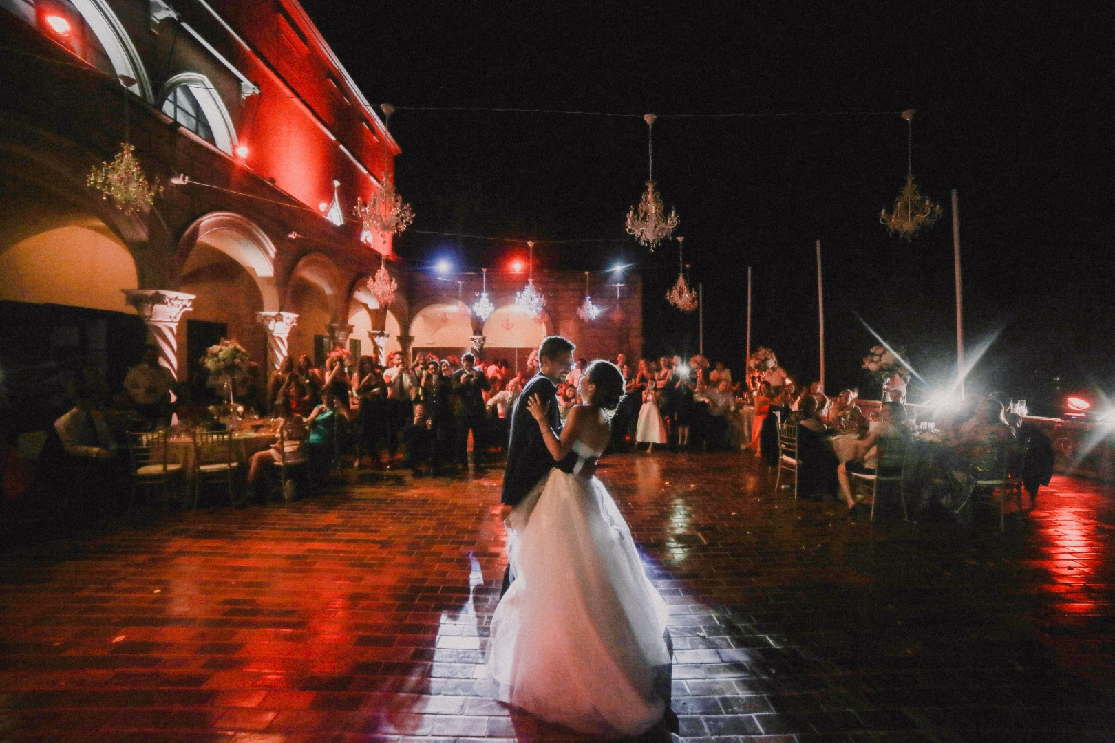 This photo shows the wedding couple dancing their first dance. The lighting is beautiful, mostly red and blue. The guests are watching and filming them.