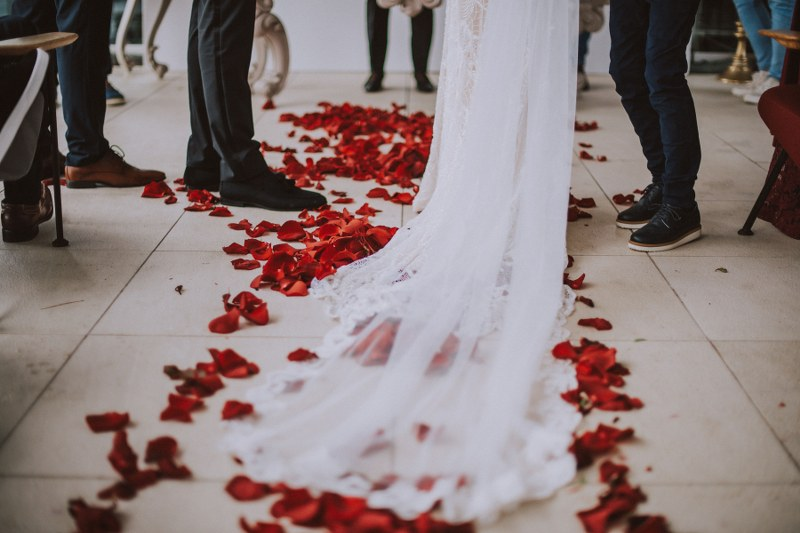 This photo shows the ground: we can see the end of the bride's dress and veil as well as dark red rose petals on the floor.