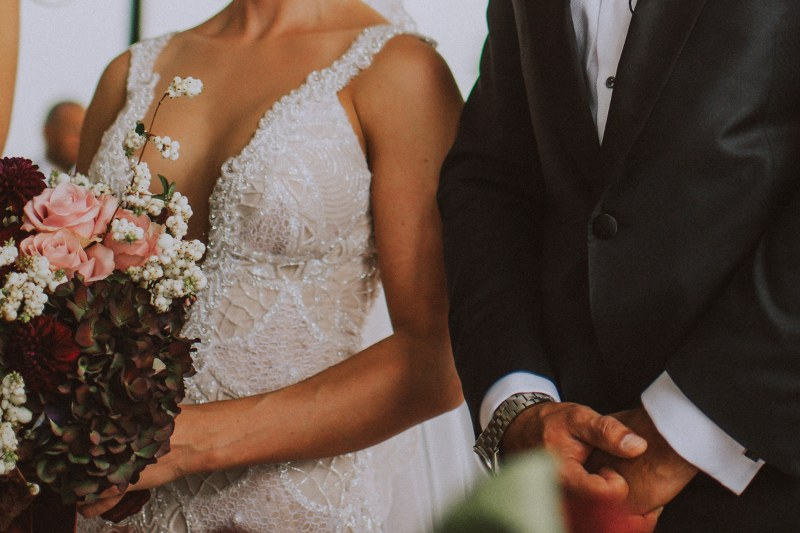 On this photo we can see the bodies of the groom and bride: his black tuxedo and her sparkling white wedding dress and bouquet.
