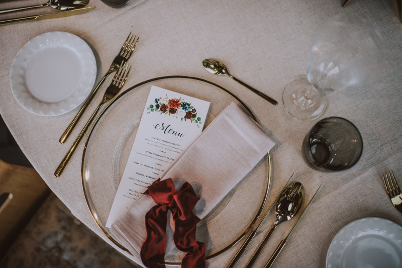 A close up of the table with just one of the plates. The plate is transparent with gold edges, and the cutlery is also golden. There's a red ribbon on the napkin, and a menu.