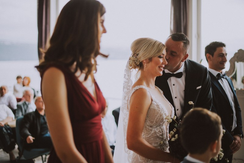 A scene from the wedding ceremony: the groom is giving the bride a kiss on the cheek while the guests are smiling.