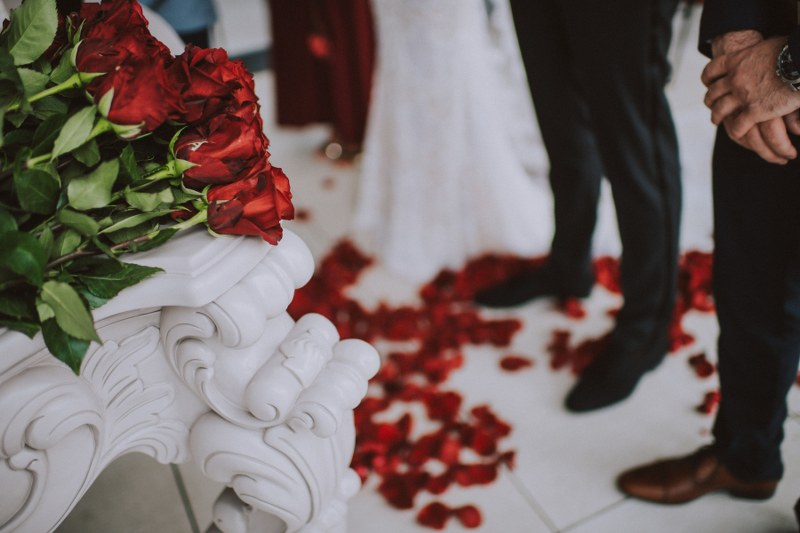 In the focus of the image are dark red roses on a white console table. In the background we can see the ground: the couple's feet and some rose petals.