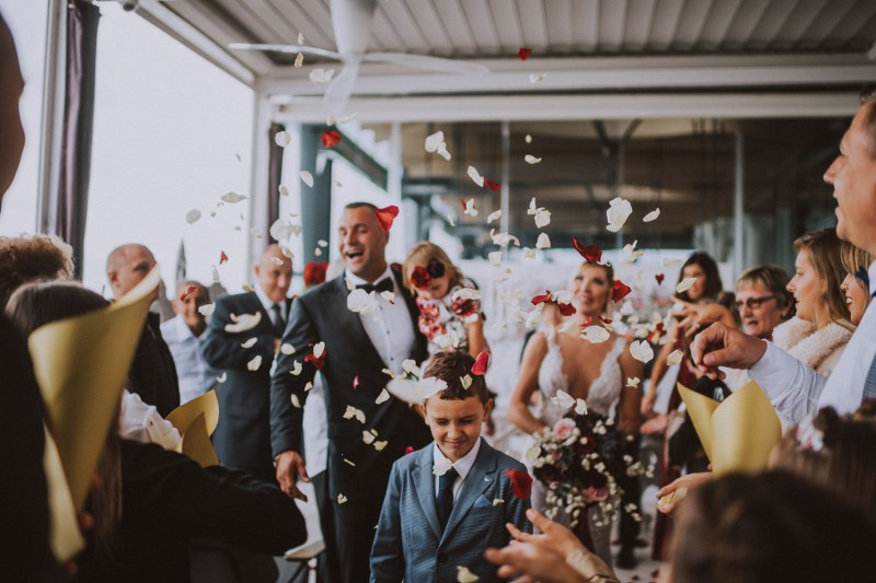 The wedding ceremony just finished and the married couple is laughing. There is a little boy who seems to be avoiding the confetti the guests are throwing. The groom is holding a little girl, their daughter.