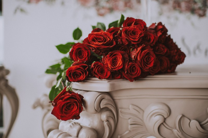 This image is a close up of some dark red roses on a beautiful white console table.