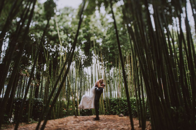 This image shows the wedding couple in the middle of some bamboo trees. The groom is picking the bride up and she is leaning on his forehead.