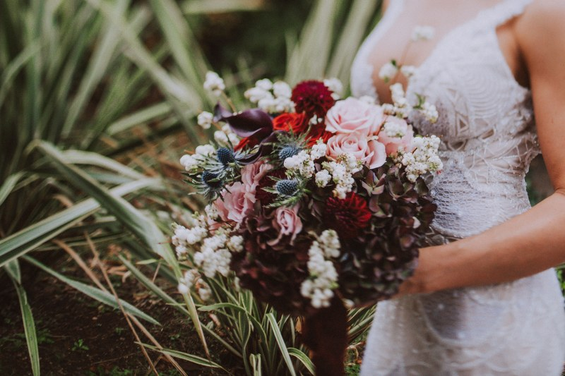 This image is a close up of a beautiful wedding bouquet: a mix of wild flowers, greenery, white and blue flowers and dark red roses with some blush pink.