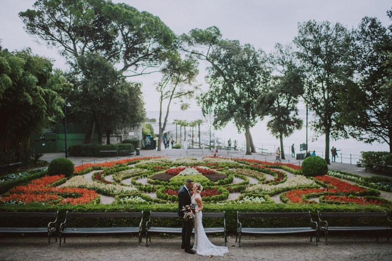 The wedding couple is in a park. They are stood in front of benches and kissing while behind them is a labyrinth of colorful flowers.