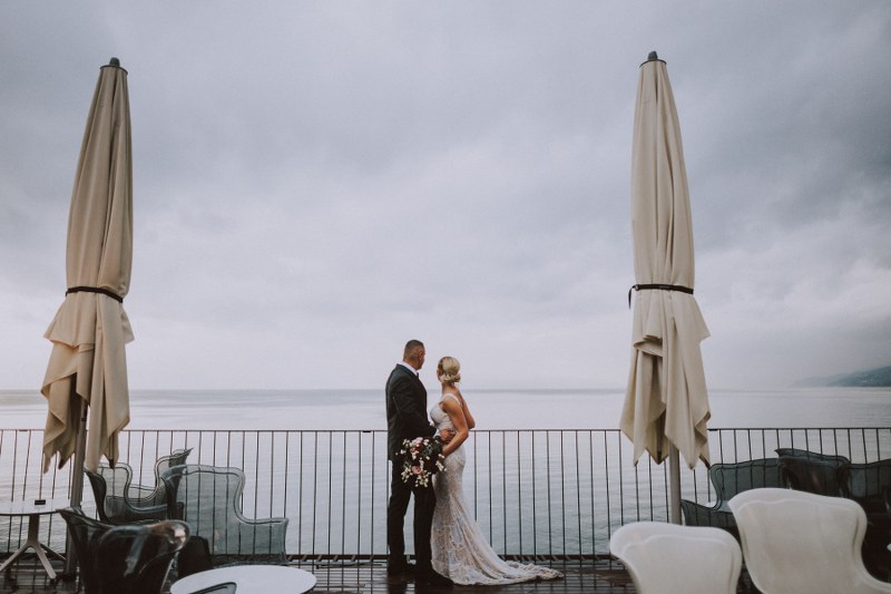 The couple is on a terrace overlooking the sea and the weather is very moody and rainy. She is holding a stunning bouquet.