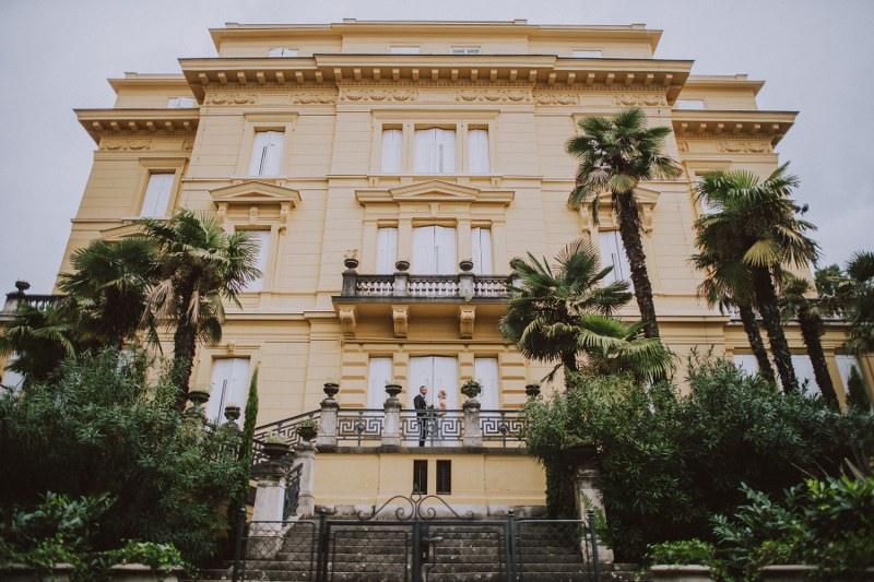 This image shows a villa in Opatija, Croatia. The architecture is simple yet stunning and there are tall palm trees in front. On the bottom balcony is our wedding couple looking at each other and smiling.