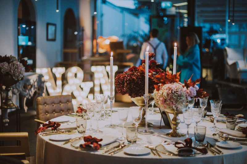 This photo shows a table set up that looks very autumnal. The flowers are dark reds and pinks. We can also see glasses and cutlery, as well as tall white candles.