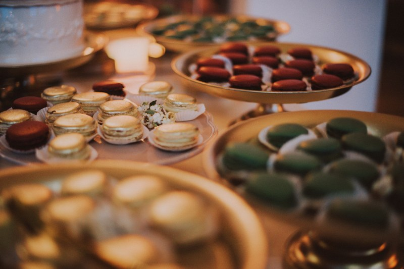 This is a close up of some tasty macarons. There are golden, dark red and dark green ones, it all looks very autumnal and in theme.