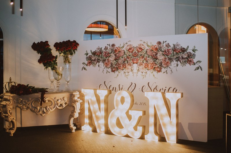 This image shows big letter signs that are lit up: the letter N & N are the initials of the married couple. On the side is a lovely white console table with vases full of dark red roses.
