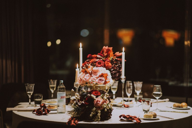 This photo shows a table set up that looks very autumnal. The flowers are dark reds and pinks. We can also see glasses and cutlery.