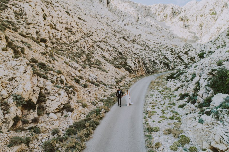 A beautiful photo from the mountains of Croatia. This is a wedding photoshoot, the couple is in the street walking and holding hands.