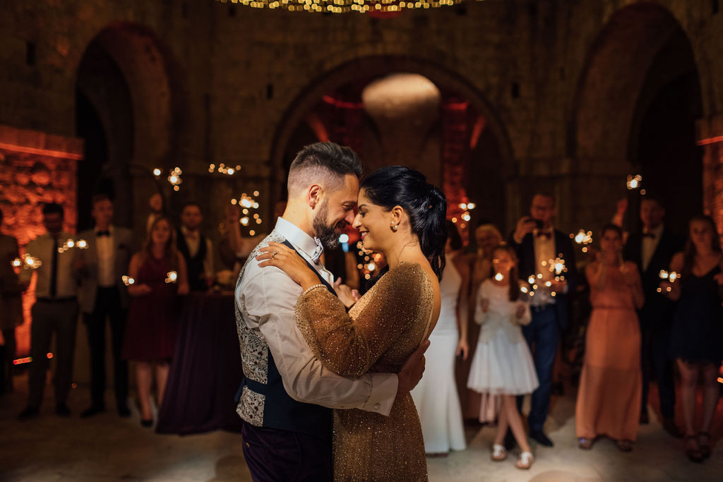 Here the couple is having their first dance. The guests behind them have sparklers in their hands. The bride has changed into a shiny rosegold party dress. They are leaning on each other's forehead and smiling.