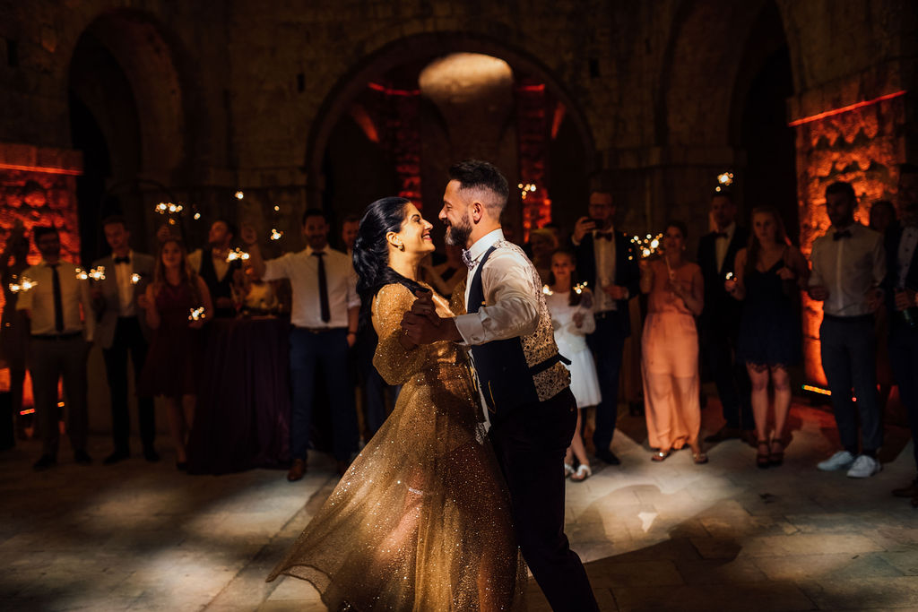Here the couple is having their first dance. The guests behind them have sparklers in their hands. The bride has changed into a shiny rosegold party dress. They dancing and laughing.