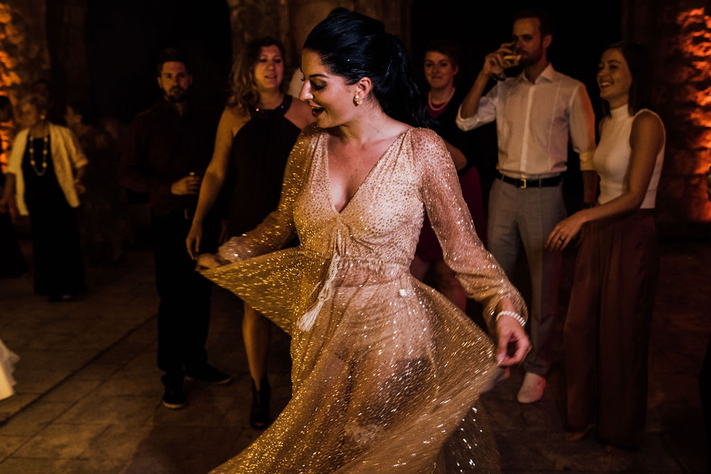 Here the bride is dancing on her own. The guests behind her are drinking, dancing and laughing. The bride has changed into a shiny rosegold party dress.