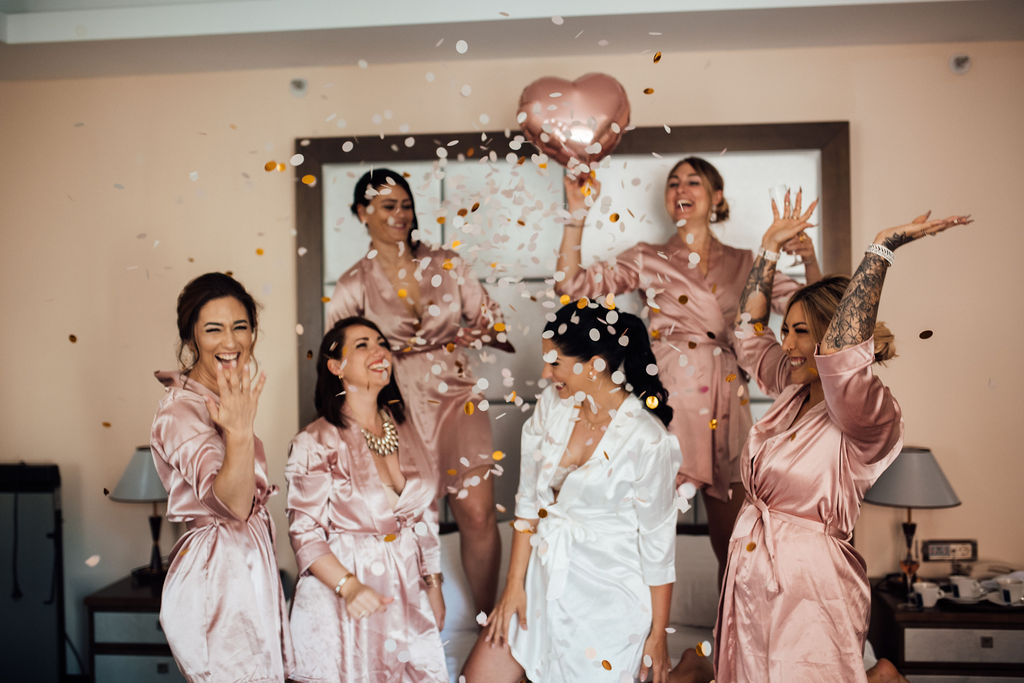 The photo shows the bride and her bridesmaids having fun. Confetti are flying all around and one of the bridesmaids is holding a pink heart-shaped balloon. The bride is wearing a white dressing robe, and the rest of them pink ones.