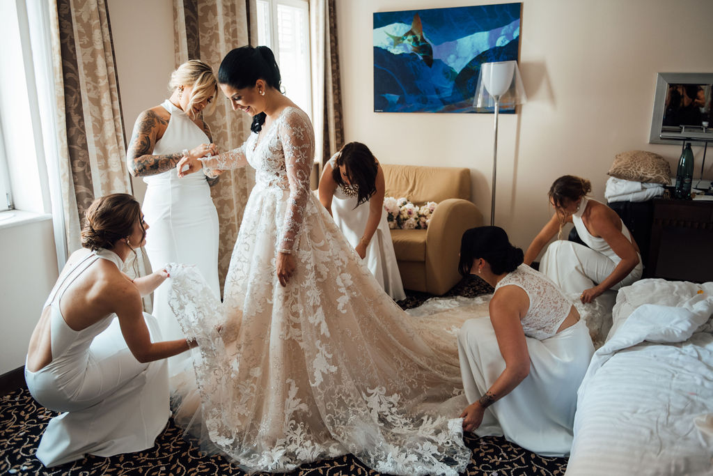 This photo shows the bride getting ready with her bridesmaids. Maria is wearing a beautiful long heavy lace wedding dress with sparkles. Her bridesmaids are all wearing similar simple white dresses. They are in a nice hotel room.