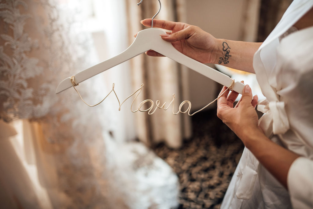 This photo shows a hanger with the bride's name: Maria. The hanger is white and simple and her name is on a rose gold piece of metal string. Behind is the wedding dress. She's wearing a white dressing robe.