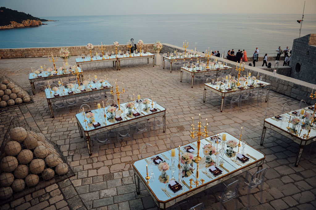 This is a photo of the upper terrace on Lovrijenac fortress in Dubrovnik. The view is the sea and Lokrum island. There are huge stone balls on one side, and on the other is the reception set up with mirror tables and transparent chairs. There are big golden candelabras on the tables.