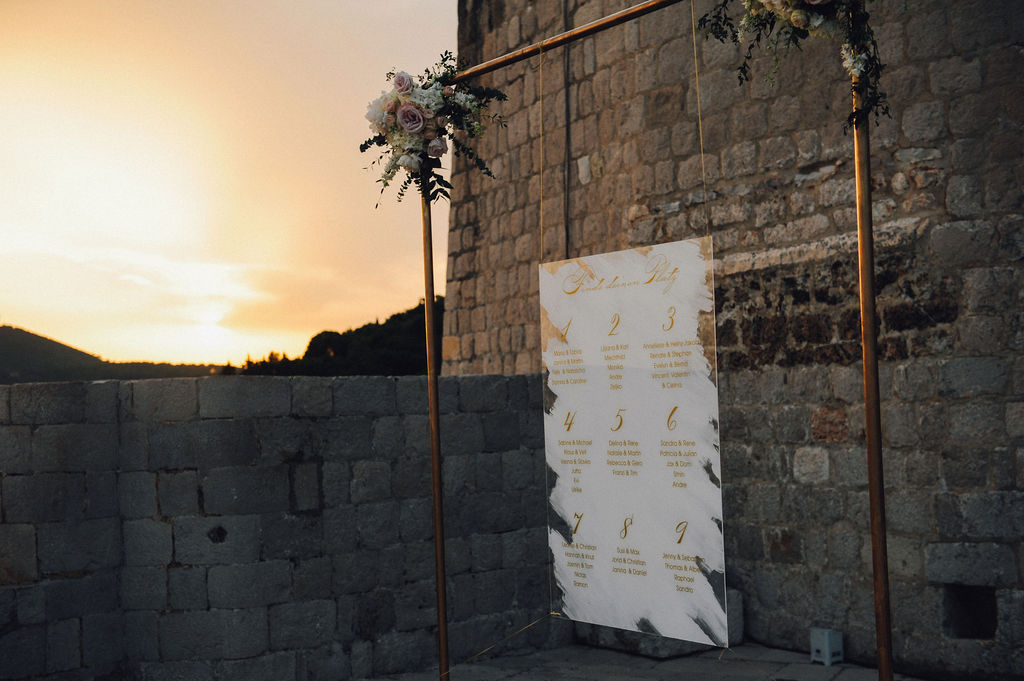 On this photo we can see the seating chart places in front of the stone wall of the fortress. Behind the sun is setting. The seating chart is in a golden frame with pink and white flower arrangements in the upper corners. The colors are rose gold.