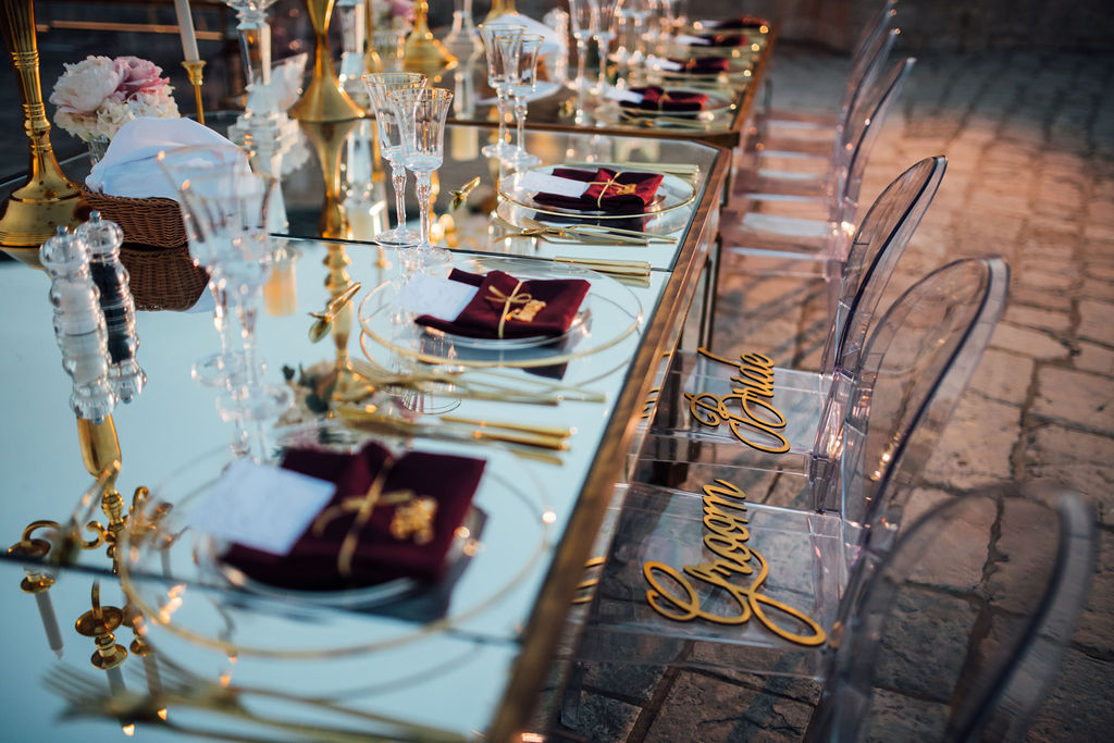 This photo shows a close up of the table with chairs. The table is mirrored and the chairs transparent. The napkins are dark red. There are signs on the chairs for the bride and groom.