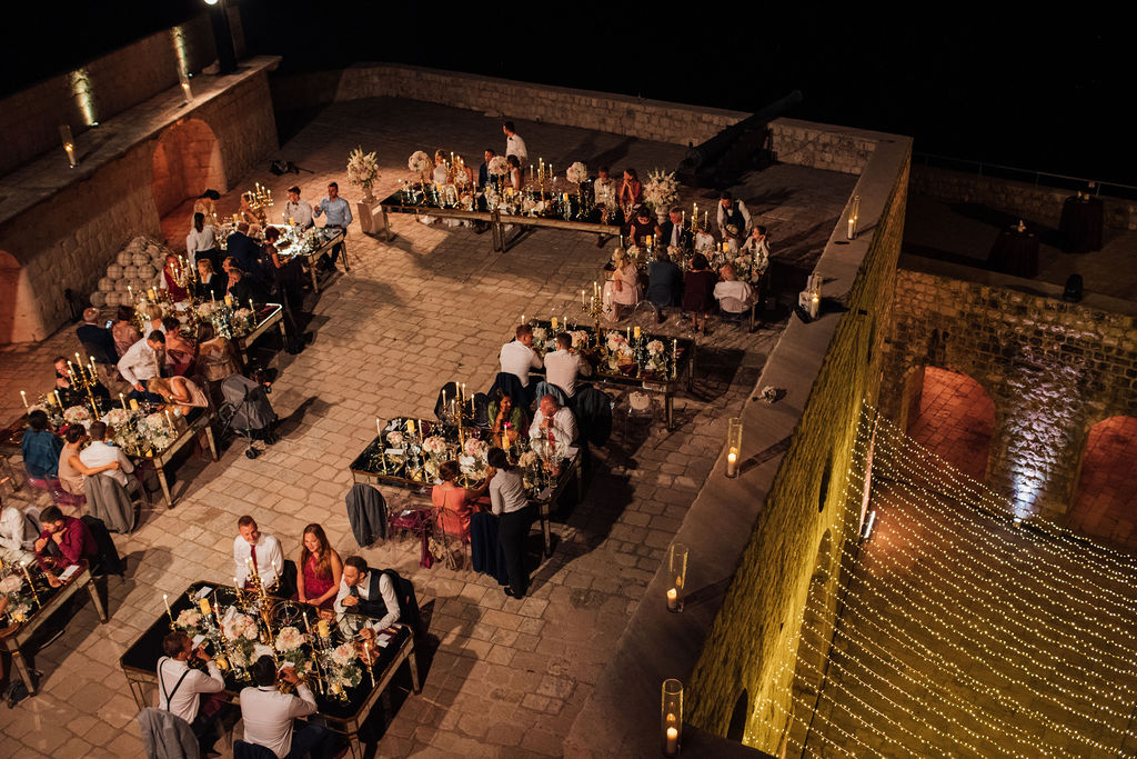 This photo shows the terrace of Lovrijenac fortress in the evening. There are string lights below the terrace and the guests are having dinner and chatting.