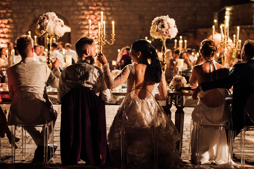 This is a photo of the bride and groom from behind. They are sitting and laughing at each other. Next to them are their friends. We can also see the golden candelabras and tall pink flower arrangements.