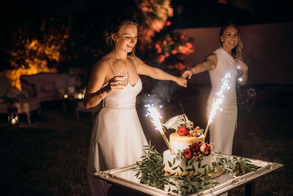 Dubrovnik bridezilla wedding cake. There are two dinosaur looking brides on top - so bridezillas. And sparklers on the side. The brides are holding hands and laughing.
