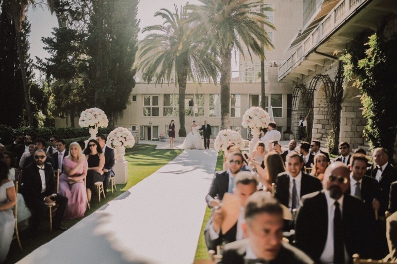 The couple is arriving to their ceremony in Dubrovnik. There's a simple white carpet across the grass. Guests are in anticipation.