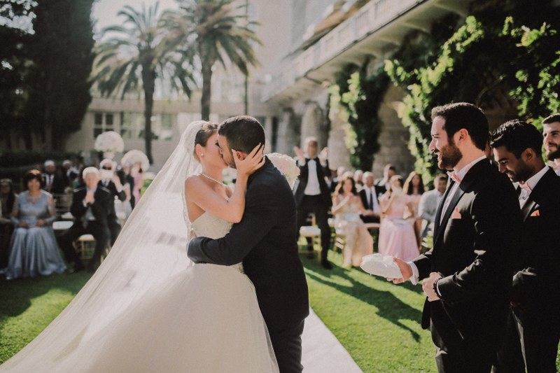This is a ceremony in the garden of Villa Argentina in Dubrovnik. The bridesmaids are wearing blush pink dresses and the bride has a big gown and veil. Guests are clapping and the couple is kissing.