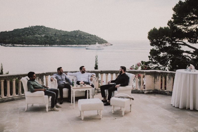 Four men are sitting on a beautiful stone terrace overlooking a green island and a boat. They are relaxing before the wedding with some beer.