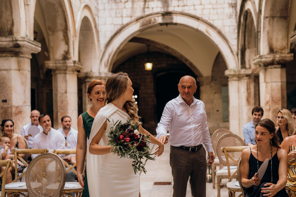 The father giving away the bride in Sponza palace ceremony, Dubrovnik. He's letting go of her hand and smiling at her, she's smiling back. The mother is happily watching them, as well as other guests.