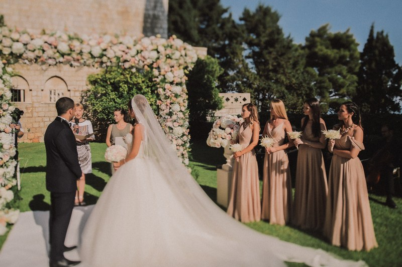 This is a ceremony in the garden of Villa Argentina in Dubrovnik. The bridesmaids are wearing blush pink dresses and the bride has a big gown and veil.