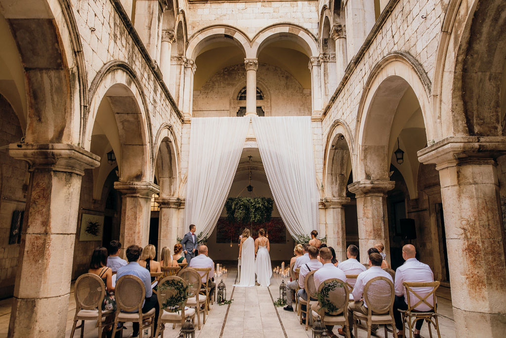 This is a photo of a same sex ceremony in Sponza palace. The two brides are in front of the officiant, under a hanging greenery arch. On the sides there are white curtains, framing the collumns. The guests are seated and listening to the ceremony.