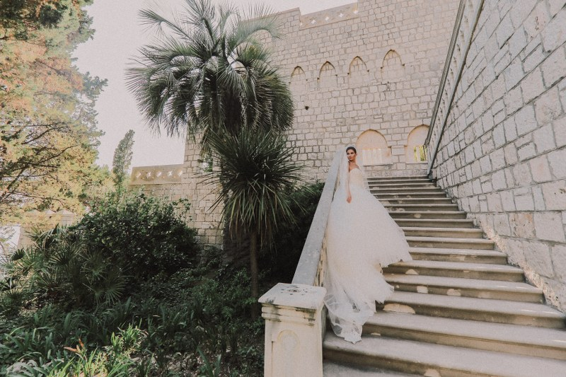 The beautiful bride is stood on a long stone staircase, wearing a huge white gown. Behind her is a stone wall and palm tress.