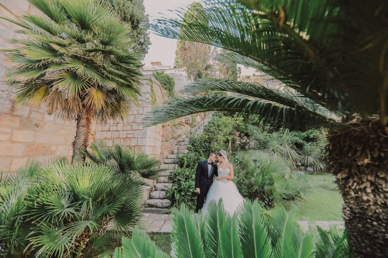 The married couple is on their photosession. Surrounded by beautiful exotic greenery, they are looking into each others eyes.