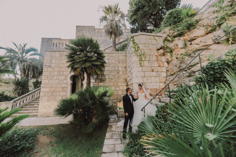The married couple is on their photosession. Surrounded by beautiful exotic greenery, they are walking down a stone staircase. Villa Sheherezada is in the background.