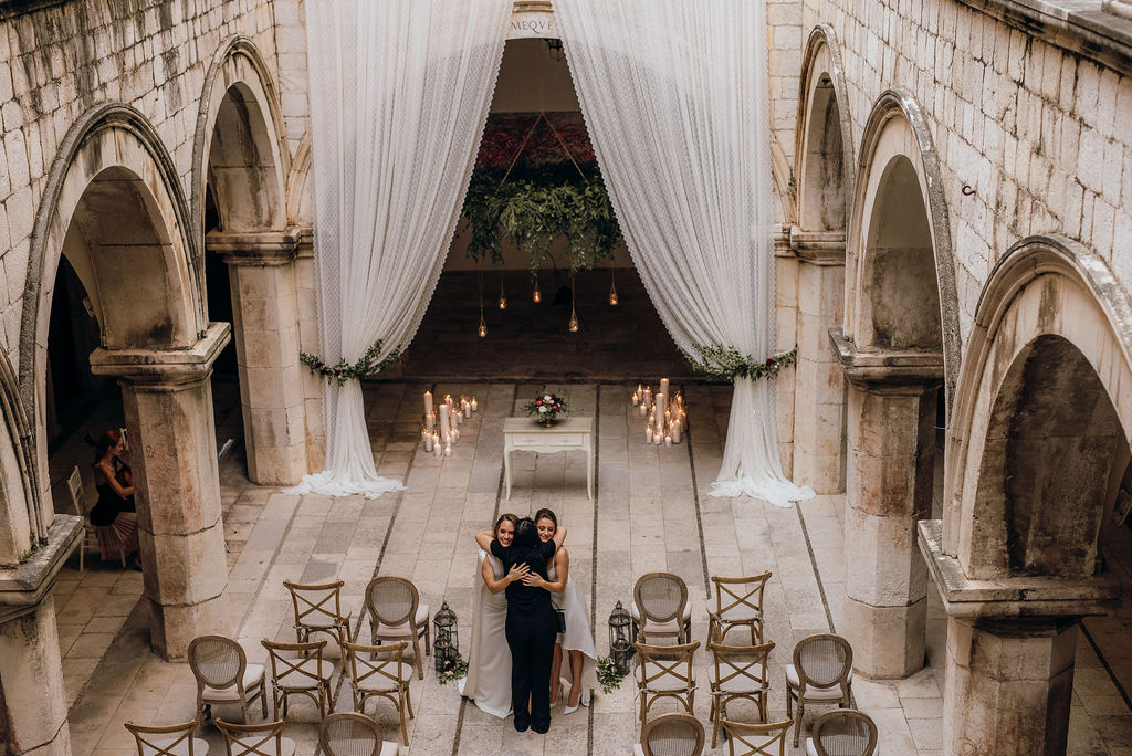 A hug between the beautiful couple and their amazing wedding planner. This is a photo of a same sex ceremony in Sponza palace. The two brides are in front of the officiant, under a hanging greenery arch. On the sides there are white curtains, framing the collumns. The guests are seated and listening to the ceremony.
