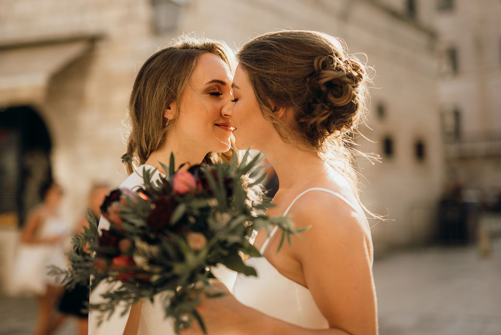 Love is love! This is a photo taken during the photoshoot of our beautiful lesbian couple. They are holding their bouquets and kissing.