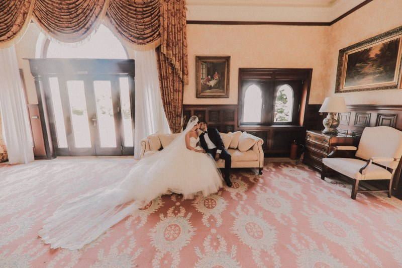 Here is the couple inside villa Sheherezada. The room is stunning: a red and gold floor, same color curtains and vintage furniture. The couple is on a white couch kissing.